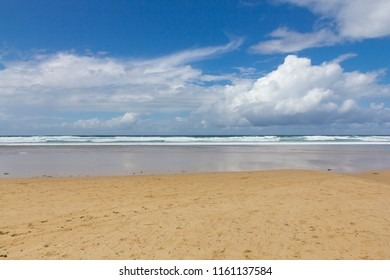 Bright summer day on a sandy beach looking out to sea with blue sky and clouds