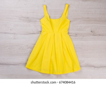Bright summer dress. Trendy yellow sarafan on wooden background.