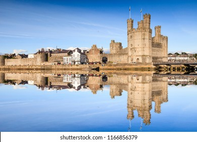 A bright summer evening at Caernarfon Castle, Gwynedd, North Wales. The castle is reflected in the River Seiont