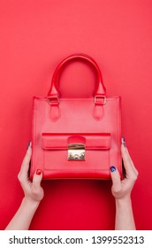 Bright summer fashion ladies accessories. Stylish red leather handbag or flap bag on a red background. Women hands with bright manicure holding bag. Top View. Flat Lay. Copy Space.