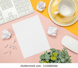 Bright summer home office workspace with blank sheet of paper in the middle. Flat lay composition on pink and yellow background.