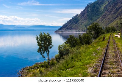 Bright summer landscape with Circum-Baikal railway on shore lake Baikal. Blurred foreground from train movement