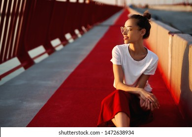 Bright summer lifestyle portrait of young pretty woman in eyewear, red skirt and white T-shirt, sitting on a bright red floor on the bridge. Trendy hipster girl relaxing, enjoying warm summer day on