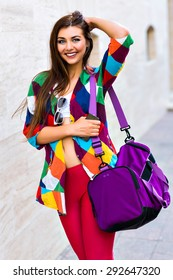 Bright summer trendy portrait of young fit girl walking on the street, wearing vivid shirt crop top and leg gins holding big sportive bag, long hairs and make up.