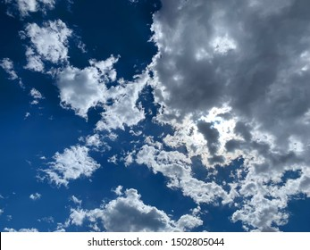Bright sun behind dramatic clouds, looking directly up at the sky. Taken near high noon.