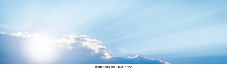 Bright sun in the blue sky with clouds panoramic view web banner.