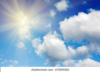 Bright sun with clouds against the blue sky