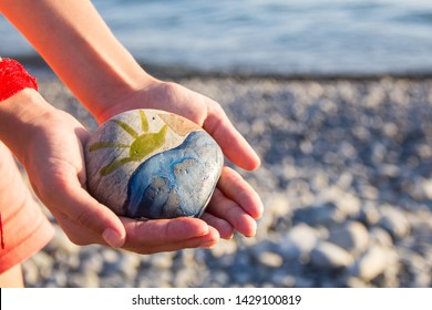 Bright sun painted on pebble in the hands of a child on the background of a pebble beach in summer