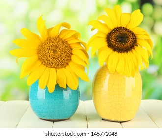 Bright sunflowers in vase on wooden table on natural background