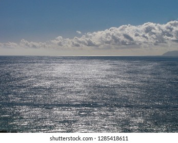 Bright sunlight, blue sky and clouds reflected in the Pacific Ocean of southern California, with Santa Catalina Island on the horizon