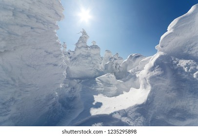 Bright sunlight rays over forests of giant Juhyo (ice trees or snow monsters) on the snowy hillside under blue clear sky in Zao hot spring (onsen) & ski resort on a sunny winter day in Yamagata, Japan