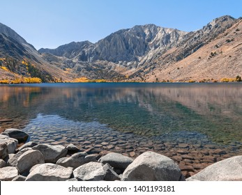 Bright sunny day at Convict Lake in autumn. Peak fall colors with reflection on the water surface. Laurel Mountain of the Sierra Nevada mountain range in the background, big rocks in the foreground.