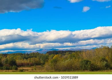 bright sunny day with puffy white clouds overlooking distant mountains with field and trees in foreground