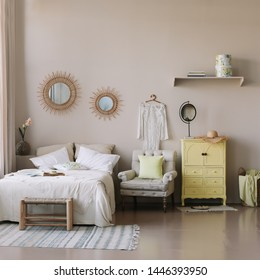 Bright and sunny modern bedroom interior with wooden furniture. Cushions, blanket and food tray on the bed, nightstand beside and hanging round mirror on the wall. Real photo