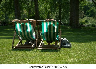 Bright sunny view of unrecognizable people sitting in striped deck chairs on a summer day in London, UK