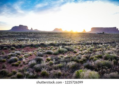 Bright sunrise in Monument Valley Utah, with lots of desert sagebrush in the foreground. Sun peaking over the rock formations