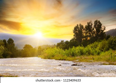 Bright sunrise in the mountains of the Carpathians, Ukraine. The rays of the sun are reflected in the mountain river. Concept ecology protection. Explore the world's beauty.