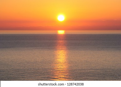 Bright sunrise under the sea surface with yellow red gradient colors