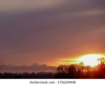 Bright sunrise with violet sky over Cascade Range in the Pacific Northwest.
