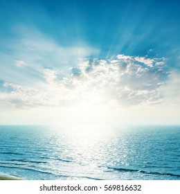 bright sunset in blue sky with clouds over sea