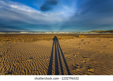 Bright sunset on the famous sandy Cannibal Beach. Shadows of photographers