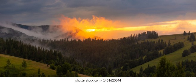 Bright sunset over foggy mountains. Vivid sun through the clouds over mountains slopes, covered with spruce forest. Wide panorama of Carpathian mountains. Ukraine.