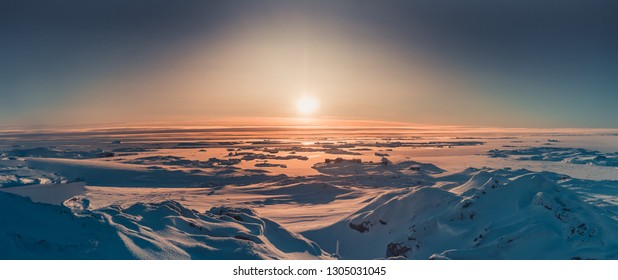 Bright sunset panorama view in Antarctica. Orange sun lights over the snow covered polar surface. Picturesque winter landscape. The beauty of the wild untouched Antarctic nature.