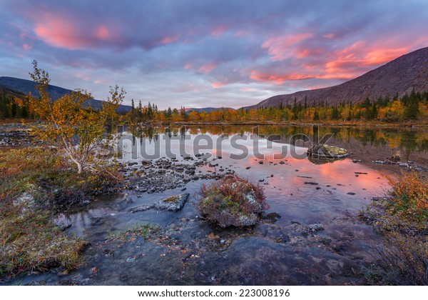 Bright sunset skies reflected in Polygonal freshwater lake in Hibiny mountains above the Arctic Circle, Russia
