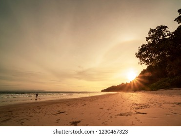 Bright sunset in a tropical island with beach, mountains and vegetation in the background