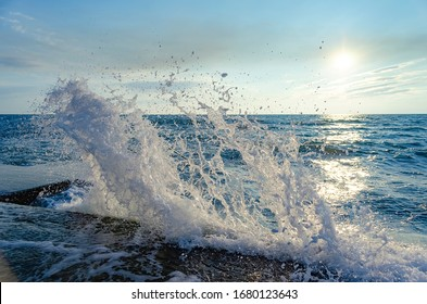 Bright sunset under the sea with waves splashes and stones.