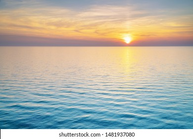 Bright sunset with yellow sun. Nature seascape.