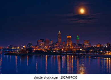 A bright super moon rises high above the city of Cleveland Ohio and Lake Erie waters at dusk