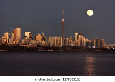 Bright supermoon over glowing Toronto skyline at sundown Toronto, Ontario, Canada - November 13, 2016