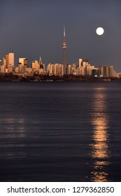 Bright supermoon and reflection with golden glowing Toronto skyline Toronto, Ontario, Canada - November 13, 2016