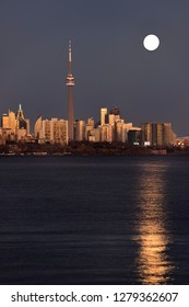 Bright supermoon and reflection in Lake Ontario with golden Toronto skyline Toronto, Ontario, Canada - November 13, 2016November 13 2016