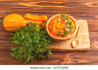 Bright tasty pureed pumpkin soup in wooden bowl with ingredients on cutting board. Healthy food concept. Rustic wooden background. Horizontal view. Copy space