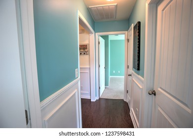 Bright Teal Interior Hallway with white wainscot.