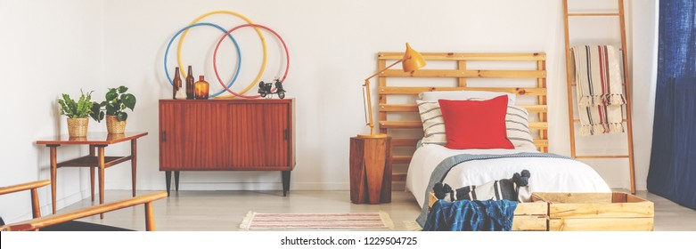 Bright teenager bedroom in real photo with retro cupboard with bottles, bed with wooden bedhead, and lamp on bedside table