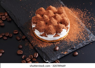 bright tiramisu on a graphite plate on a black background contrasts beautifully appetizing meal dessert menu scattered cocoa