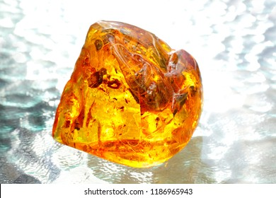 A bright transparent glowing piece of yellow amber on the  background from waves. Sunstone. Ancient petrified resin. Natural mineral crystal for jewelry. Amber with inclusions. Amber light