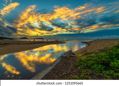Bright tropical cloud reflections at the Waialae Beach Park in Kahala, Hawaii, at dawn - see the faint red sun rising behind the cloud cover