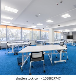 Bright university communal study room with white desks, chairs and big tv