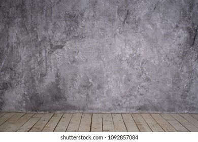 Bright vintage loft interior with wooden floor, textured aged grey plaster concrete on the wall. Empty