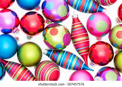 Bright vivid background of assorted Christmas ornaments with polka dot and striped patterns in a random pattern on white in a full frame view