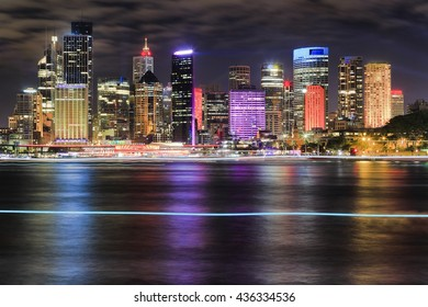 Bright wall of skyscrapers in Sydney city CBD above Circular quay across blurred harbour waters at night reflecting lights in water.