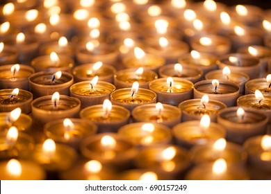 Bright warm glow from candle flames. Many beautiful lit tealight candles glowing with a golden yellow light.