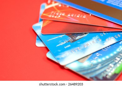 Bright wealth: macro of credit cards isolated on red background