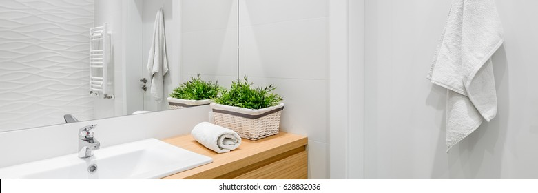 Bright and white bathroom with wooden vanity cabinet, panorama