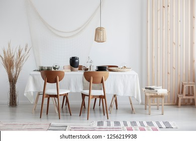 Bright and white dining room with wooden furniture and natural materials