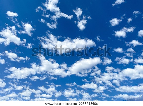 bright white fluffy clouds in the blue sky as overcast sunny high noon day scene